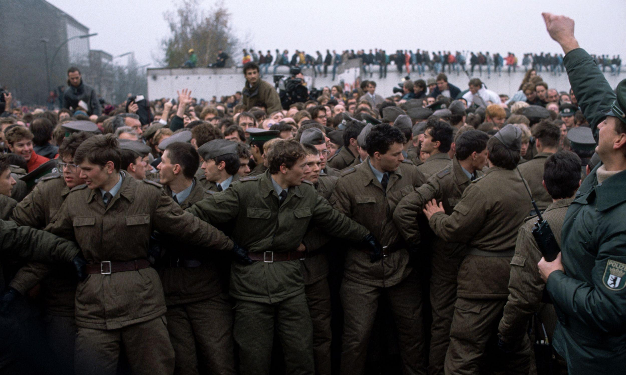 Strażnicy graniczni i tłumy przy murze berlińskim, po otwarciu granic między RFN a NRD. 1989 rok. Fot. Peter Turnley/Corbis/VCG via Getty Images
