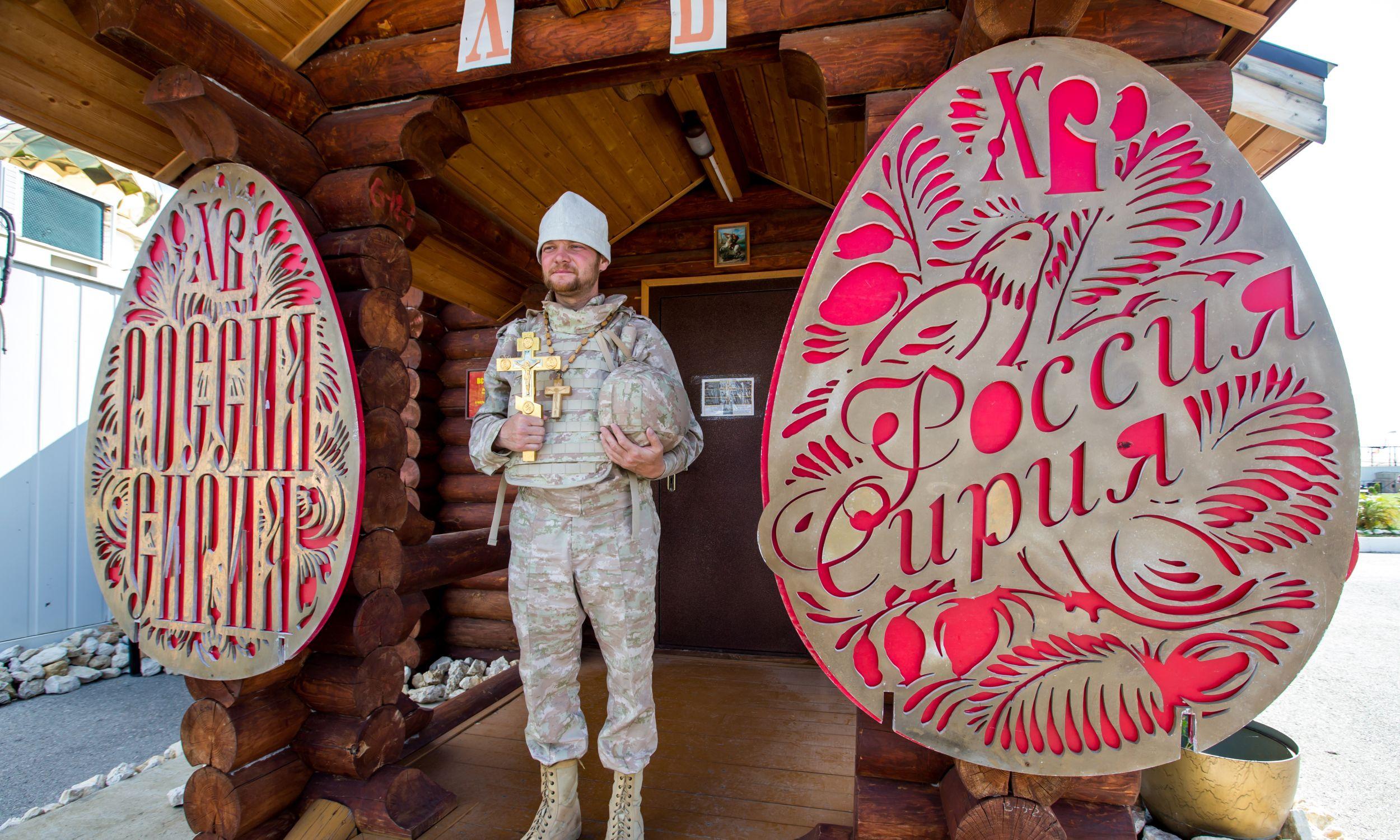 Pop z krucyfiksem przed kaplicą w rosyjskiej bazie wojskowej w Hmeimim. Fot. Getty Images/Marina Lystseva/TASS