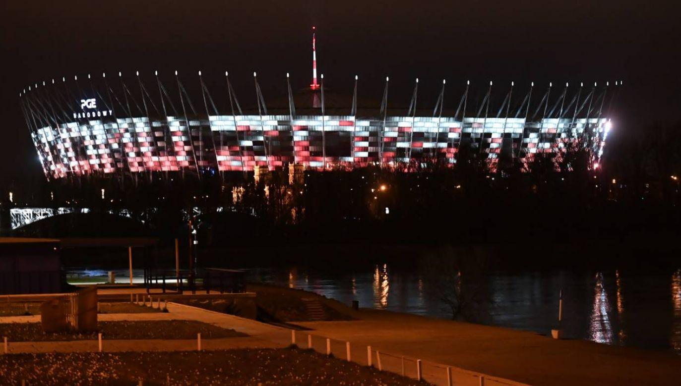 """Na fasadzie stadionu PGE Narodowy w Warszawie wyświetlane zostało hasło """"zostań w domu"""" fot. PAP/Piotr Nowak)"""