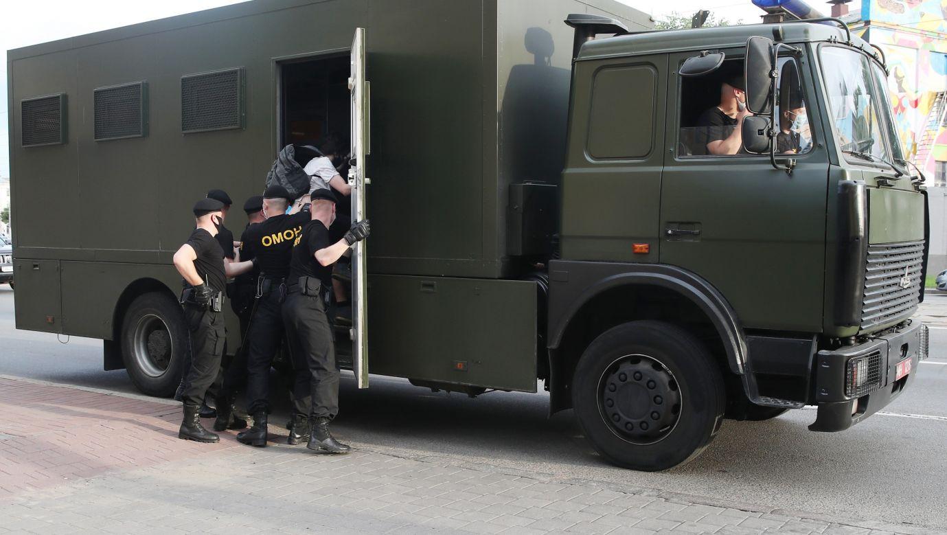 Funkcjonariusze OMON wprowadzają zatrzymanych w Mińsku demonstrantów do więźniarki. Fot. Natalia Fedosenko\TASS via Getty Images