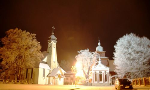 Wielkim wizjonerem Tylicza był ks. Władysław Kowalczyk, proboszcz od 1924 do 1946 roku. Prognozował, że Tylicz zostanie uzdrowiskiem i apelował o niesprzedawanie ziemi wokół źródeł.  Na zdjęciu nowy (za nim zbudowano drogę na Golgotę)  i po prawej zabytkowy, drewniany kościół p.w. św. Piotra i Pawła z roku 1612 (w 1936 dobudowano nową wieżę). W ołtarzu głównym znajduje się tu cenny obraz Matki Bożej Tynieckiej z XVI w., słynący łaskami. Na  murowanej dzwonnicy herb Tylicza. Fot. Janusz Kieblesz
