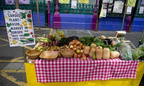 """Tablica """"Największy rynek roślinny w Europie. Bez mięsa od 2019 roku"""" na warzywnym straganie, który Animal Rebellion ustawiła na Smithfield Market, największym hurtowym targu mięsnym w Wielkiej Brytanii, działającym od  średniowiecza. Fot. Ollie Millington / Getty Images"""