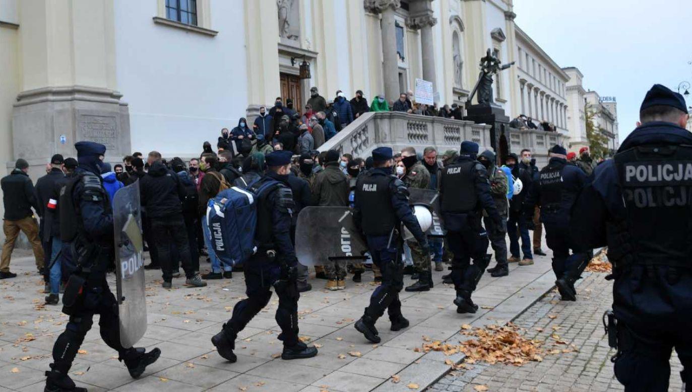 Funkcjonariusze policji i przedstawiciele środowisk narodowych przed kościołem św. Krzyża (fot. PAP/Radek Pietruszka)