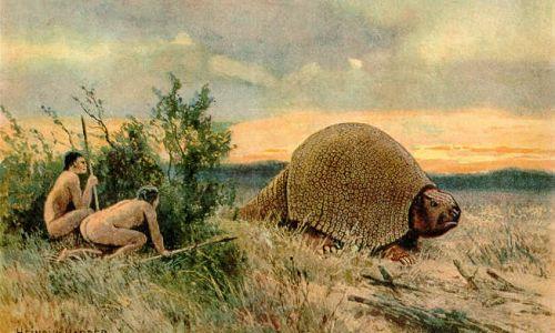 Glyptodon i polujący na niego ludzie. By Heinrich Harder (1858-1935) - The Wonderful Paleo Art of Heinrich Harder, Domena publiczna, https://commons.wikimedia.org/w/index.php?curid=1143767