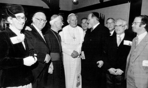 Papież Jan Paweł II wraz z biskupem Thomasem Hollandem z Salford (trzeci z lewej), spotkał się z Naczelnym Rabinem Zjednoczonego Królestwa Sir Immanuelem Jakobovitsem (czwarty od prawej) i innymi żydowskimi dygnitarzami, w klasztorze nazaretanek w Manchesterze. Fot. PA Images via Getty Images