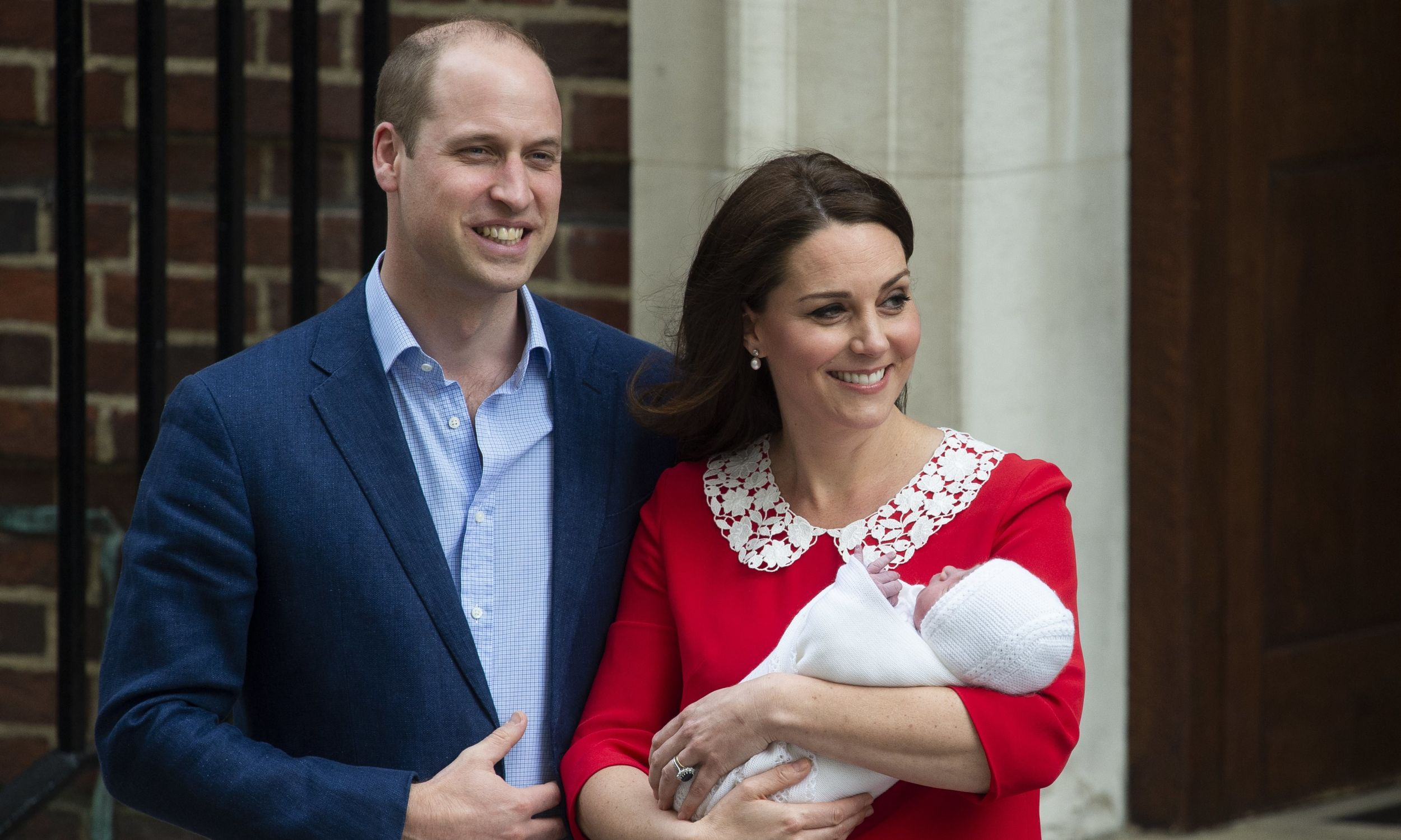 """Książę Cambridge William wraz z żoną, księżną Catherine, która trzyma nowo narodzonego syna. Stoją przed """"Lindo"""", skrzydłem szpitala św. Marii w Paddington, w zachodnim Londynie.  Chłopiec jest trzecim dzieckiem książęcej pary i piąty w kolejce do brytyjskiego tronu. Fot. PAP/EPA/WILL OLIVER"""