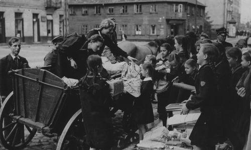 Dzieci jednej z warszawskich szkół, ładują na wóz Polskiego Białego Krzyża przy ul. Konopackiej zebraną przez siebie makulaturę. W tle drewniany dom przy ul. Małej 15 róg ul. Konopackiej. Uzyskane ze sprzedaży makulatury pieniądze zasilą fundusz biblioteczny PBK na zakup książek do świetlic żołnierskich. 13 czerwca 1939 r. Fot. NAC/IKCm sygn. 1-W-2134