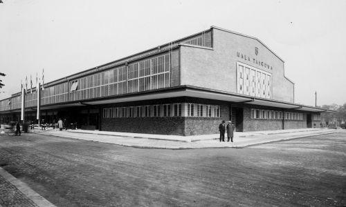 Hala Targowa w Katowicach przy ul. Piotra Skargi 6 (w dniu poświęcenia, 30 września 1936). Na budowę hali, która miała ucywilizować handel targowiskowy, przeznaczono teren po zasypanym stawie hutniczym w centrum Katowic, na zachód od Hali Mięsnej. Projektantem szkieletu o łukowej, spawanej konstrukcji stalowej był Stefan Bryła. W momencie otwarcia hali dla klientów (15 kwietnia 1937) był to największy obiekt tego typu w Polsce. Gruntownie przebudowano go w latach 2013–2015. Fot. NAC/IKC, sygn. 1-G-5631-4