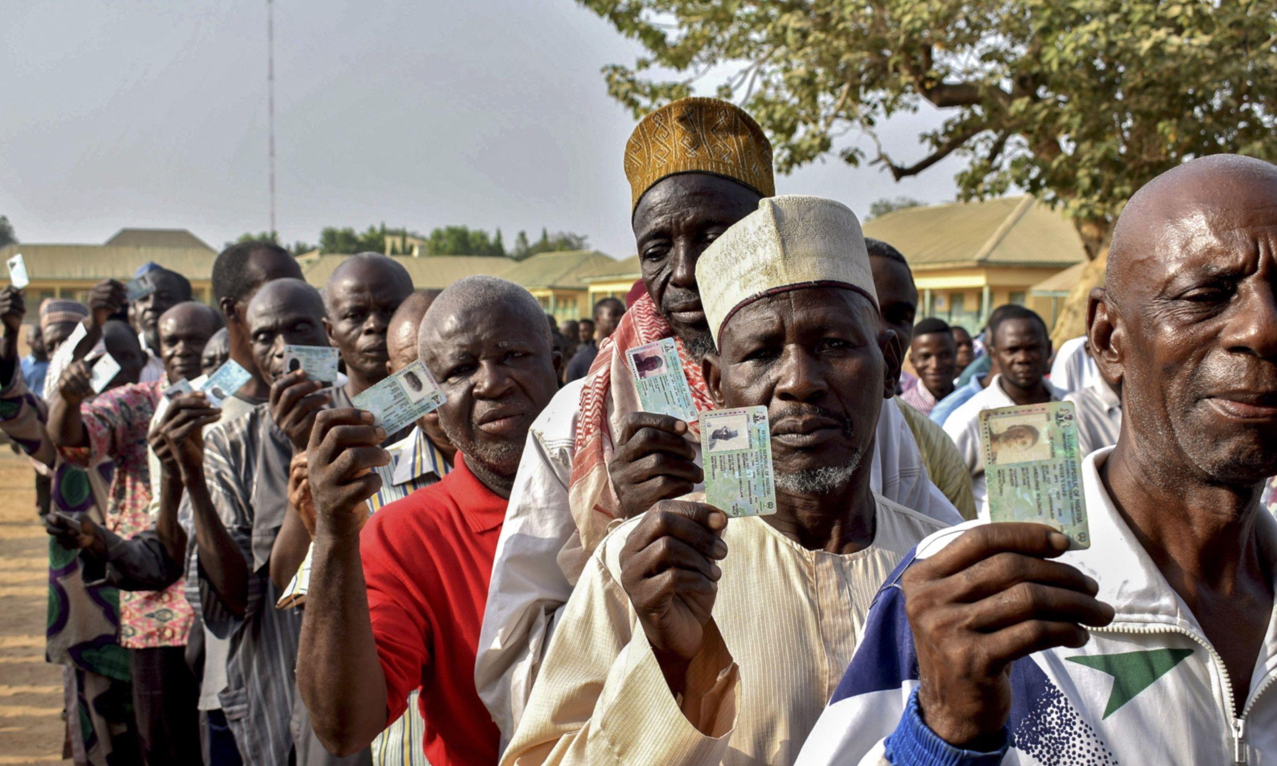 Nigeryjczycy pokazują swoje dokumenty upoważniające do głosowania w wyborach prezydenckich i parlamentarnych, Nigeria, 23 lutego 2019 r. Fot. PAP / EPA/STR