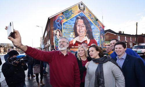Marzec 2017, mural w Belfaście przedstawiający  Bobby Sandsa, przywódcę irlandzkiego strajku głodowego w 1981 r. jest uważany za męczennika, który sprzeciwiał się Brytyjczykom. Zdjęcie przed malunkiem robią sobie: ówczesny przywódca Sinn Fein Gerry Adams (centrum), obecna liderka Mary Lou McDonald (po prawej) i i jej zastępczyni Michelle O'Neill (druga od lewej). Fot. Charles McQuillan / Getty Images)