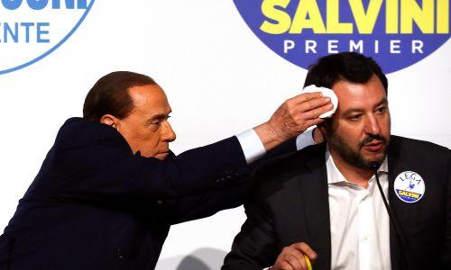 Silvio Berlusconi wyciera pot z czoła Matteo Salviniemu podczas wspólnej konferencji w Rzymie, w marcu 2018 r. Fot. REUTERS/Alessandro Bianchi