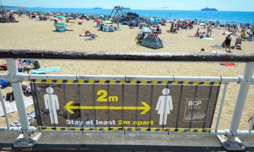 Czy turyści będą przestrzegać nakazów zachowania dystansu, o których przypominają ostrzeżenia przy plażach? Bournemouth w Wielkiej Brytanii, 25 czerwca 2020 roku. Fot. Finnbarr Webster / Getty Images