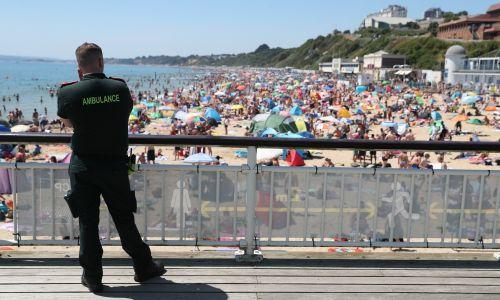 Ratownik medyczny patrzy z molo w Bournemought na tłumy gromadzące się na plaży. Fot. Andrew Matthews / PA Images via Getty Images